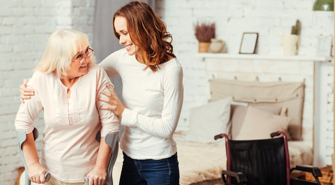 caregiver assisting an old woman to walk