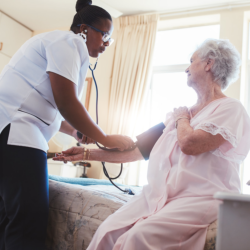 caregiver checking the blood pressure of elderly patient